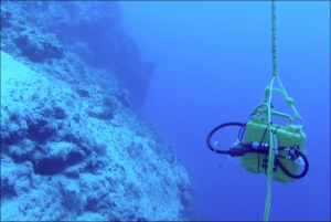 The battery box dangling above a steep reef drop off (image from ROV's front camera)